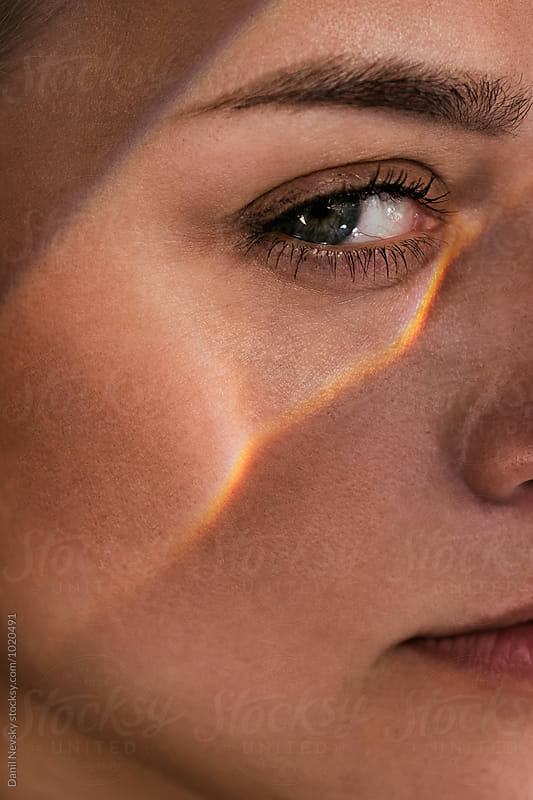 Close-up of woman's face with light under eye by Danil Nevsky for Stocksy United
