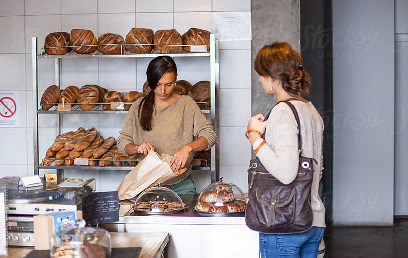 Woman buying bread in a bakery. by Mosuno for Stocksy United