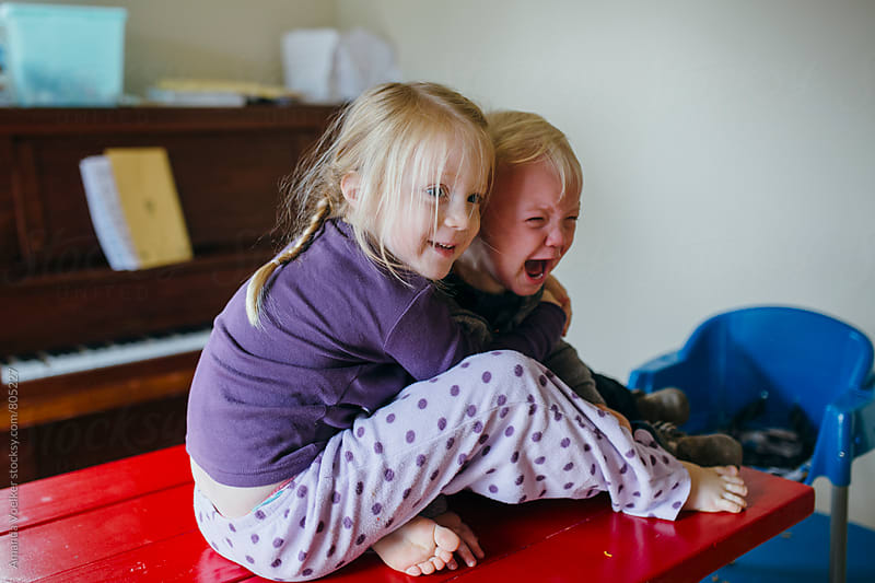 A Little Girl Hugs Her Toddler Brother as He Screams by Amanda Voelker for Stocksy United