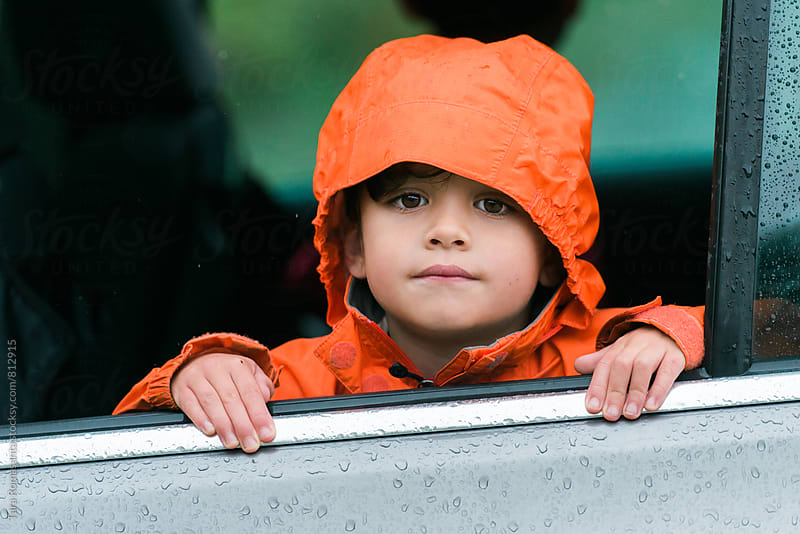 young child in orange raincoat looking out an open car window by Tara Romasanta for Stocksy United