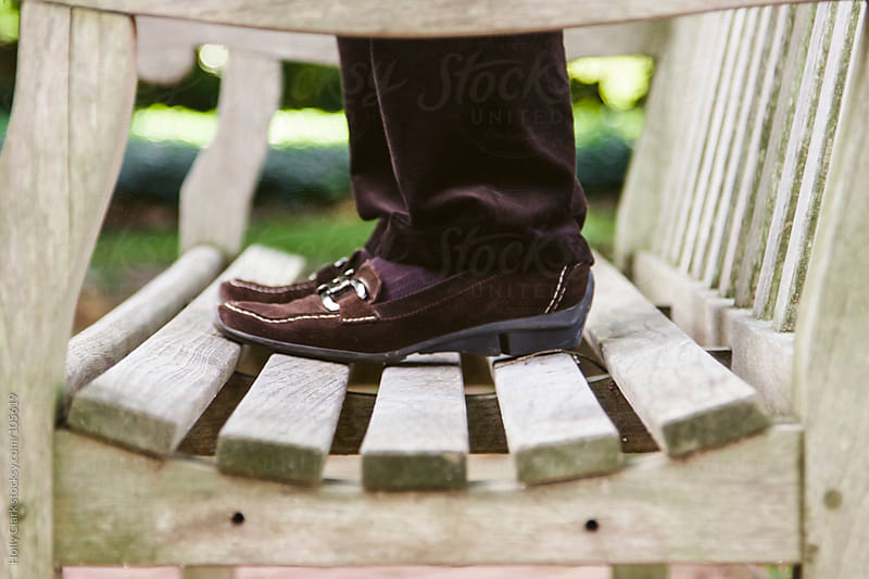 Woman wearing brown shoes stands on a bench. by Holly Clark for Stocksy United