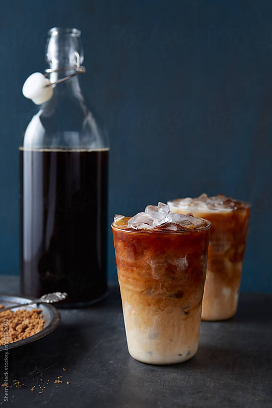 Iced lattes in glass with swirls shown with brown sugar and carafe of coffee by Sherry Heck for Stocksy United