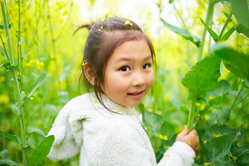 little asian girl in the rape flower field by cuiyan Liu for Stocksy United