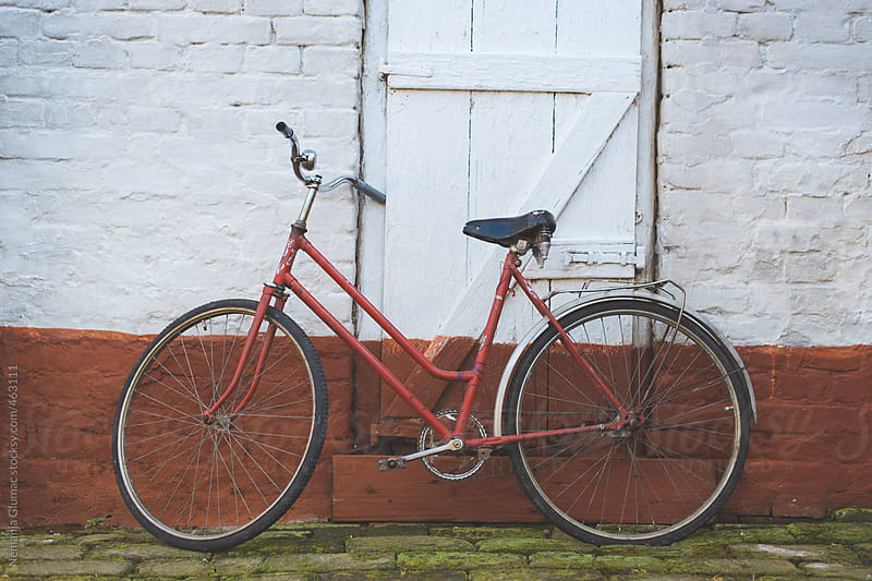 Very Old Red Bicycle Leaning to a Red and White Wall by Nemanja Glumac for Stocksy United