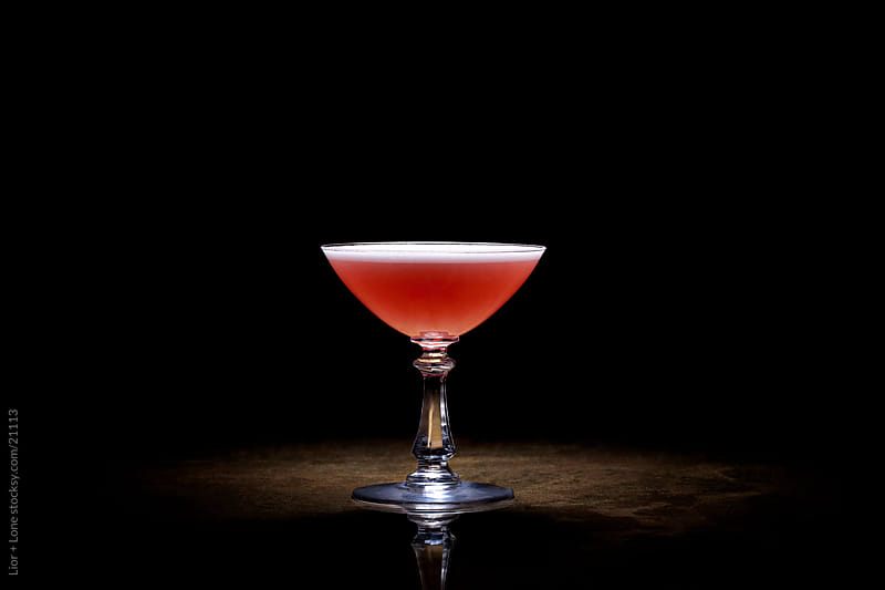 Red cocktail in martini glass by Lior + Lone for Stocksy United