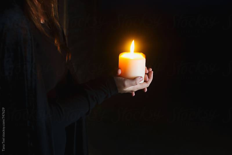 person holding lit candle in the dark by Tana Teel for Stocksy United