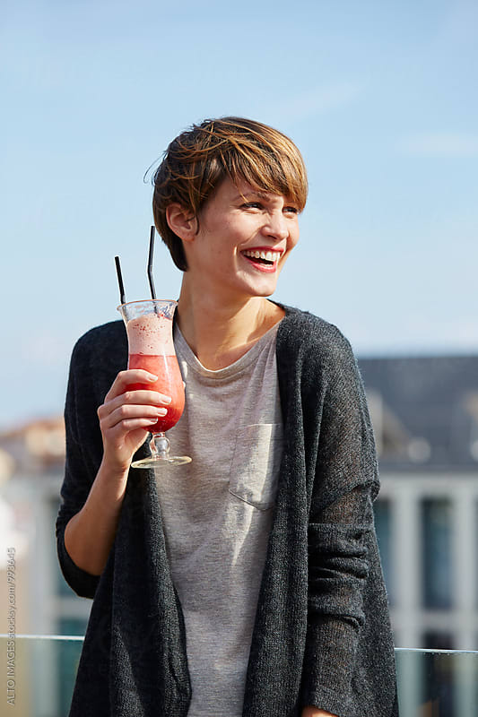 Smiling Woman Holding Cocktail Glass On Hotel Terrace by ALTO IMAGES for Stocksy United