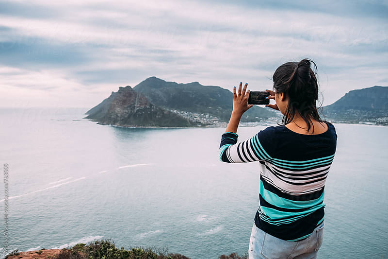 Woman taking a photo with her cell phone overlooking the ocean by Micky Wiswedel for Stocksy United