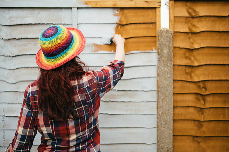 Woman painting a fence by kkgas for Stocksy United