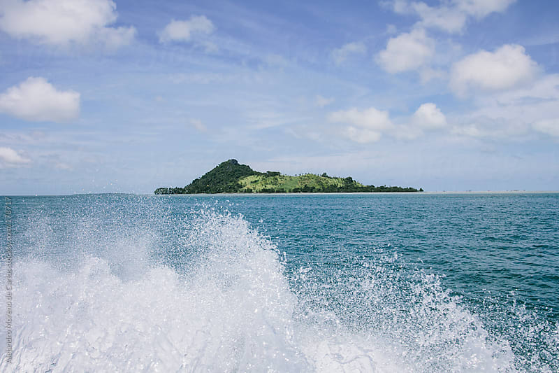 Green tropical island seen from a motor boat on the sea by Alejandro Moreno de Carlos for Stocksy United