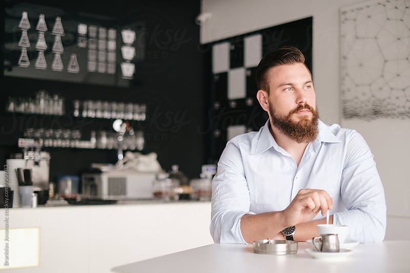 Handsome  Bearded Man Sitting at the Cafe by Branislav Jovanović for Stocksy United