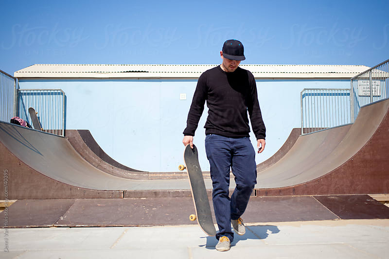 Young man walking away from a halfpipe after a skateboarding session by Denni Van Huis for Stocksy United