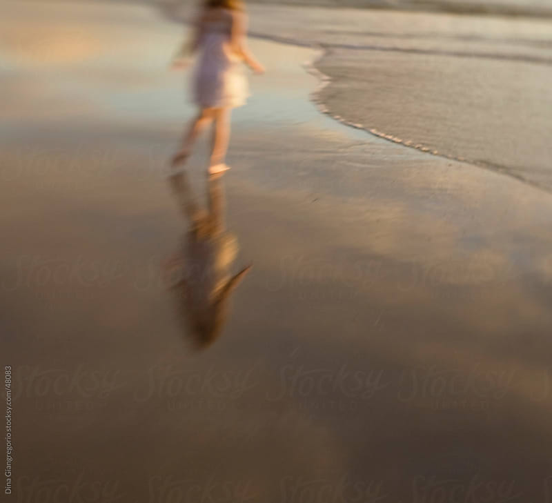 Girl in white dress walking away on beach in ocean with her reflection showing by Dina Giangregorio for Stocksy United