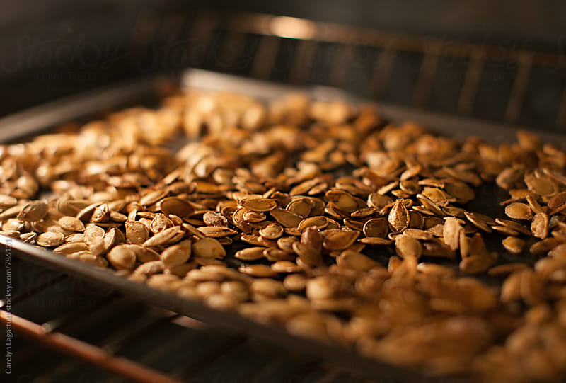 Roasted pumpkin seeds in the oven by Carolyn Lagattuta for Stocksy United