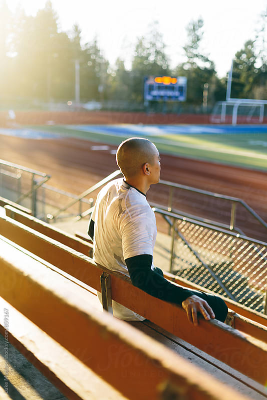 Athletic Man Sitting In Bleachers Looking Over Track And Field At Stadium by Luke Mattson for Stocksy United