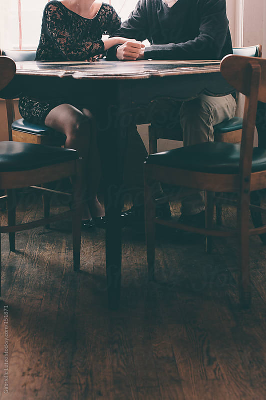 Couple at a Table holding hands - Crop by Gabrielle Lutze for Stocksy United