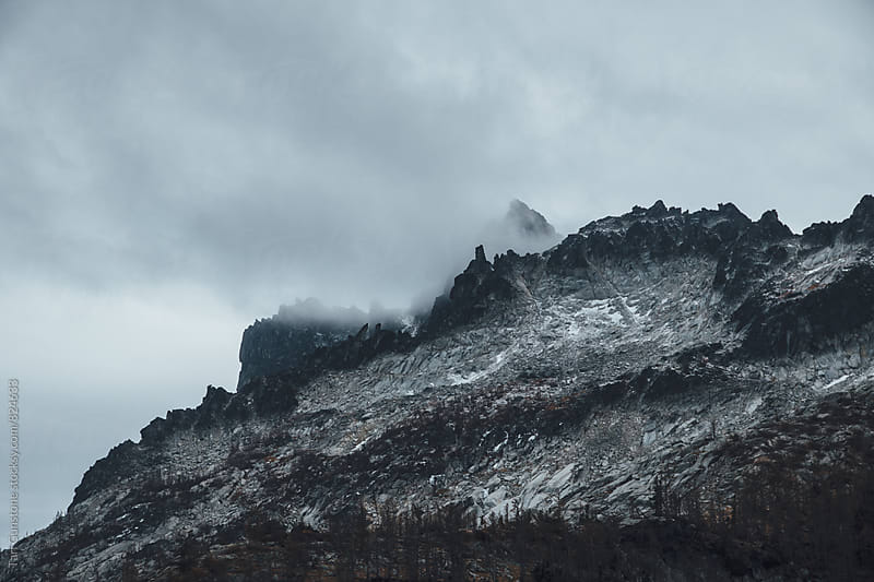 peaks in distant snow storm by Tari Gunstone for Stocksy United