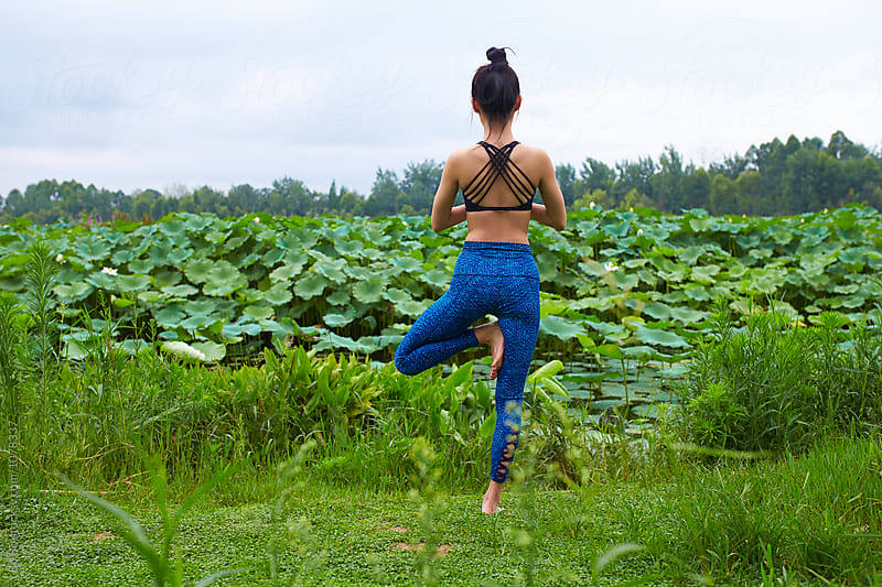 young asian or Chinese woman exercise Yoga by the side of lotus pond by Bo Bo for Stocksy United
