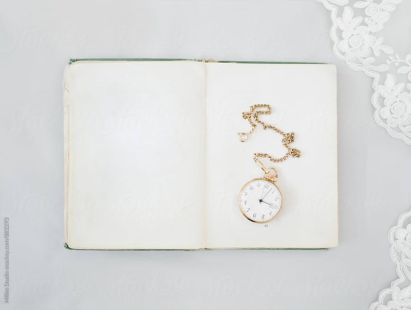 Golden watches on book by Milles Studio for Stocksy United