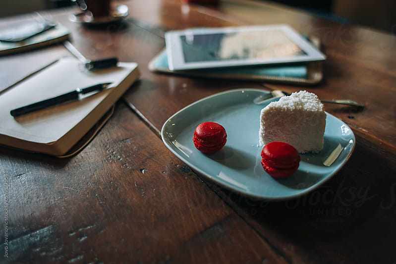 Still life - table with tablet, notebook and cakes by Jovo Jovanovic for Stocksy United