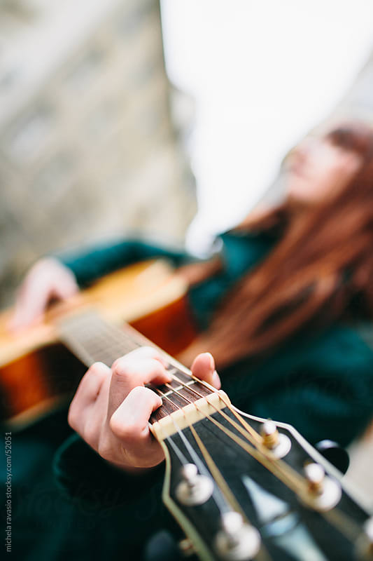 Young woman playing a guitar by michela ravasio for Stocksy United
