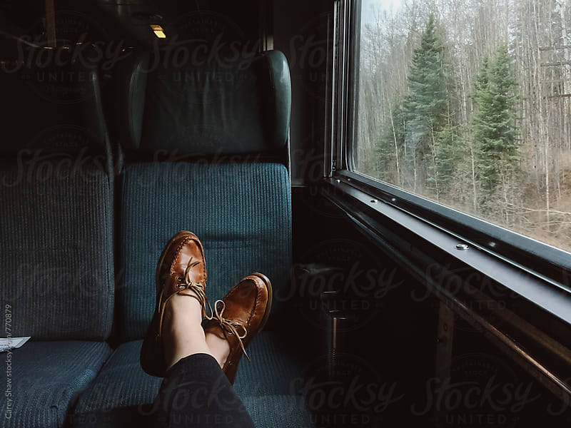 Feet resting on train seat by Carey Shaw for Stocksy United