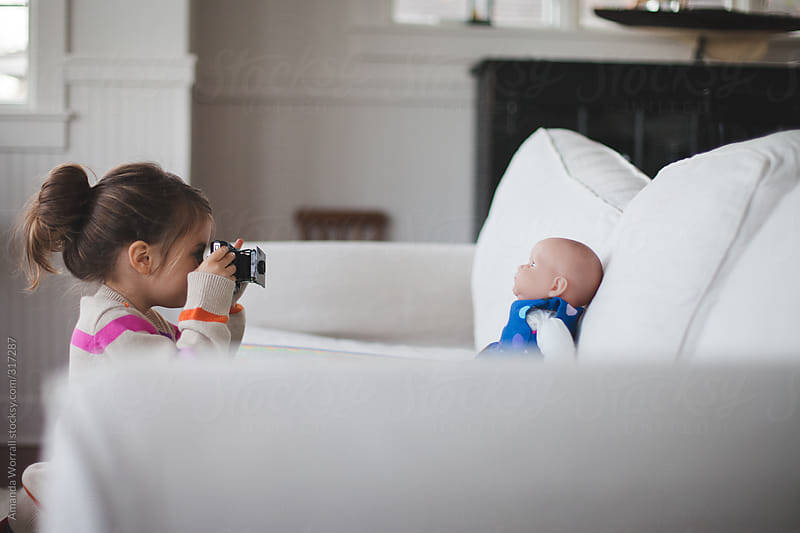 Young girl setting up a photoshoot of her baby doll on the couch at home by Amanda Worrall for Stocksy United