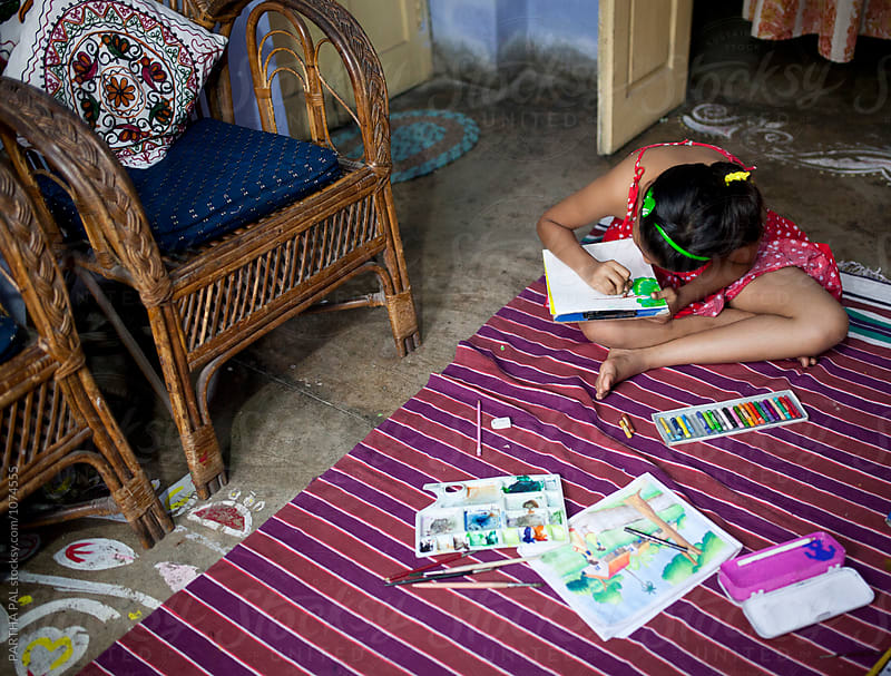 A teenager making painting work inside room by PARTHA PAL for Stocksy United