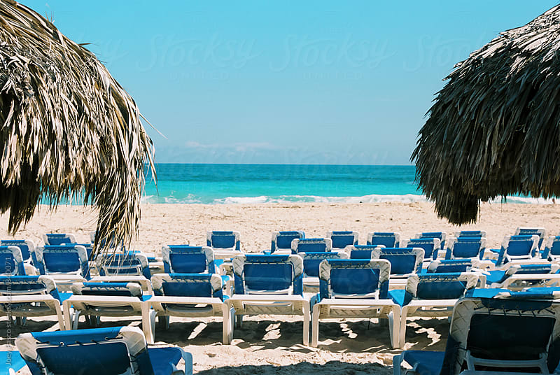 Two Palapas / Umbrellas flanking rows of empty beach chairs on a Caribbean beach by Joey Pasco for Stocksy United