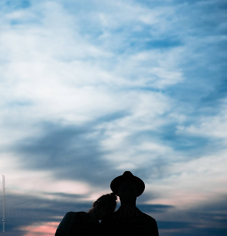 Silhouette of couple with clouds, colorful sky and sunset. by Jeremy Pawlowski for Stocksy United
