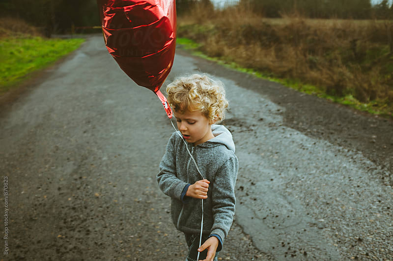 Little boy walking with balloon by Bryan Rupp for Stocksy United