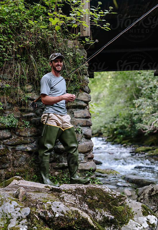 Man smiling while fly-fishing near bridge by Matthew Spaulding for Stocksy United