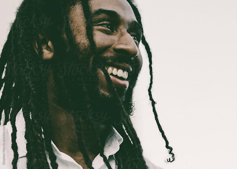 Smiling Young Man with Dreadlocks by Stephen Morris for Stocksy United