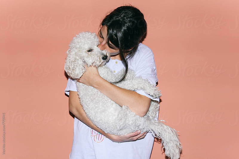 Brunette woman hugging and kissing her dog  by VeaVea for Stocksy United
