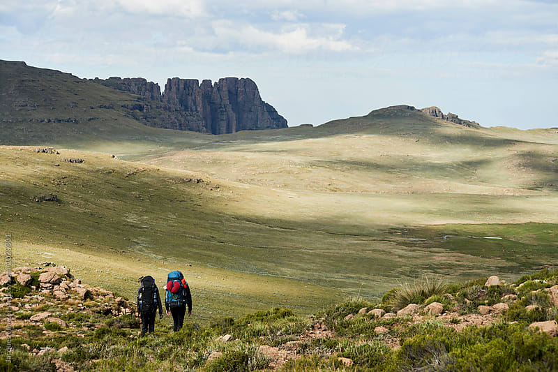 Two hikers with backpacks  by Jacques van Zyl for Stocksy United