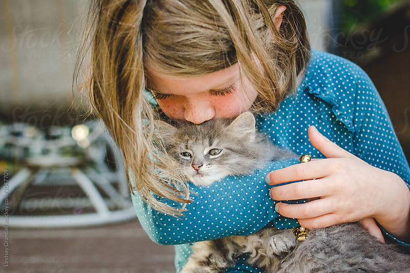 Young child holding and kissing a kitten on the head by Lindsay Crandall for Stocksy United