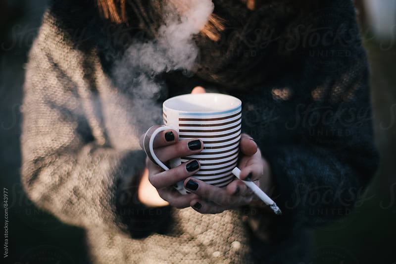 Female hands holding a cup of coffee and cigarette  by Marija Mandic for Stocksy United