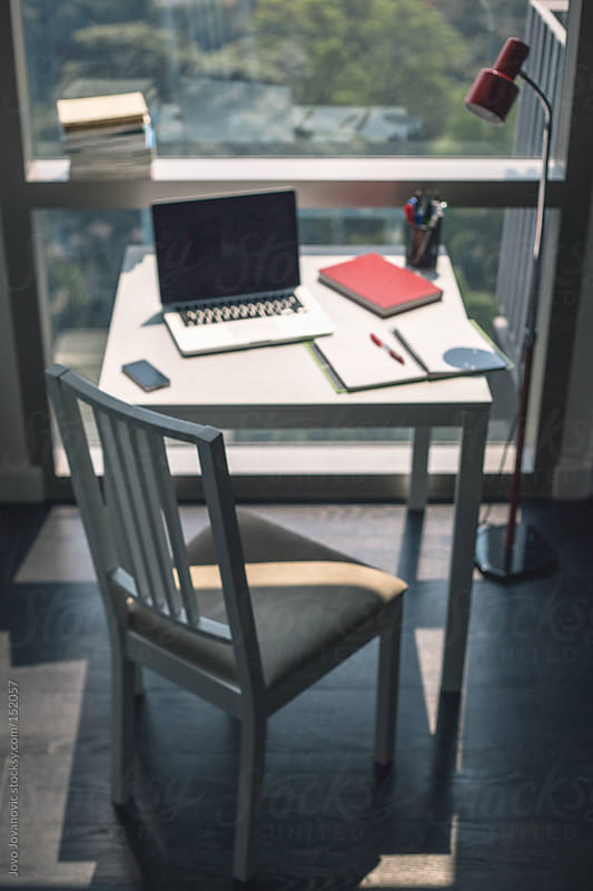 Vertical shot of a programmers work desk next to the window by Jovo Jovanovic for Stocksy United