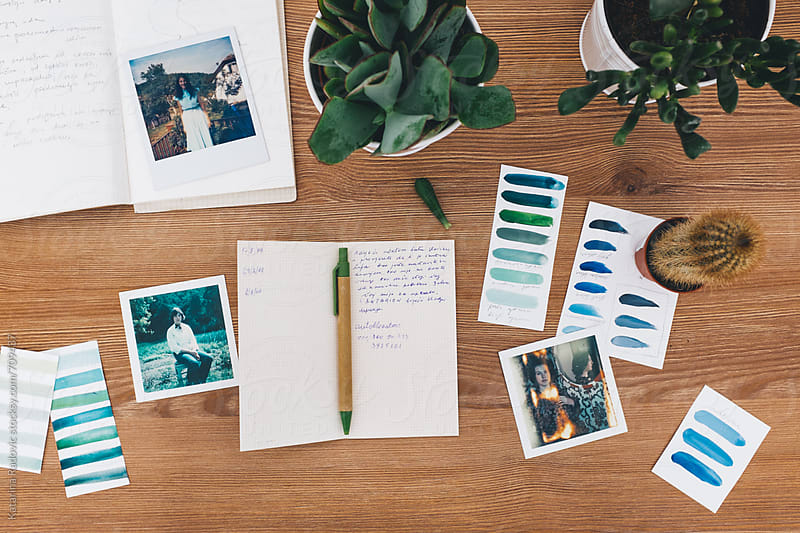 Vintage Polaroids and Notebook on a Wooden Surface by Katarina Radovic for Stocksy United