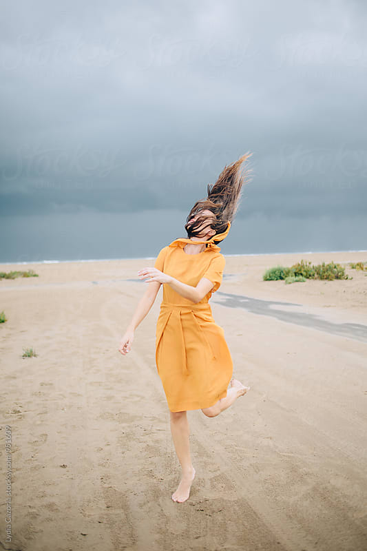 Young happy woman jumping on the beach with a yellow vintage dress by Lydia Cazorla for Stocksy United