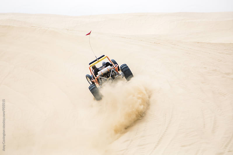 The rear view of a sand rail driving fast  by Amy Covington for Stocksy United