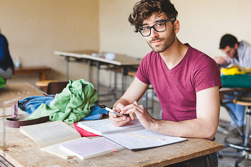 College Student at Desk with Mobile Phone by Giorgio Magini for Stocksy United
