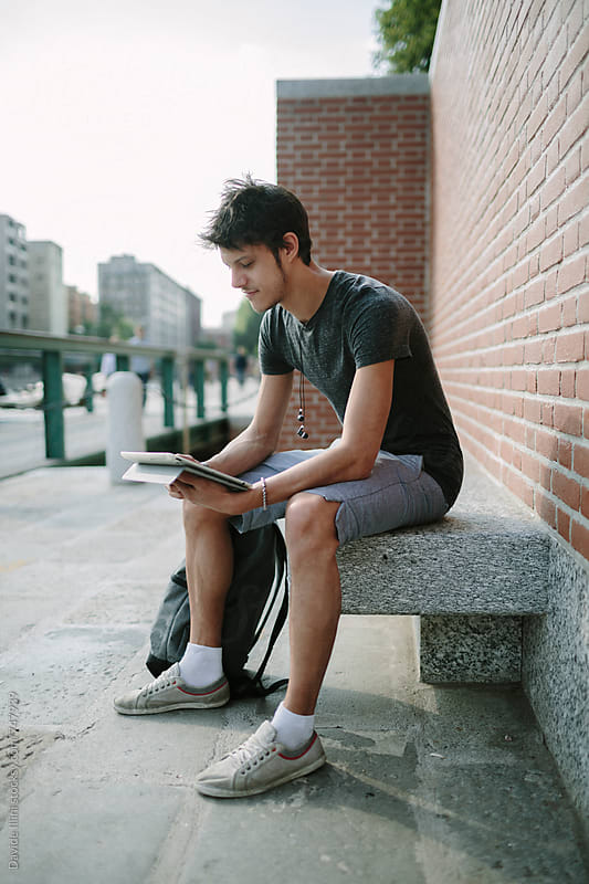 Young man using digital tablet by Davide Illini for Stocksy United