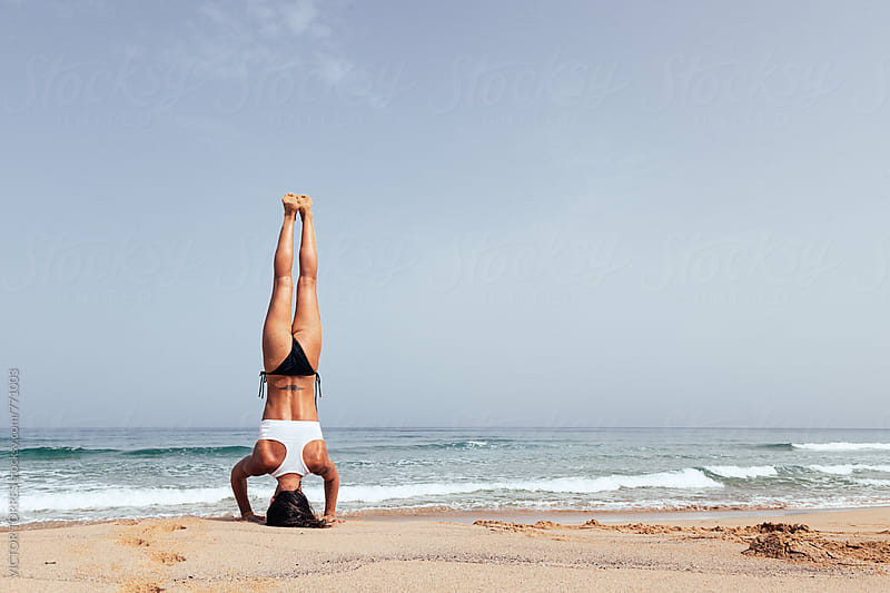 Woman Doing Yoga Exercises at the Beach by Victor Torres for Stocksy United