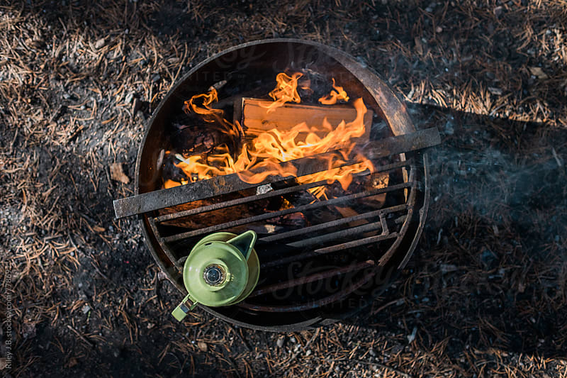 A enameled kettle sits atop a camp fire viewed from above by Riley J.B. for Stocksy United