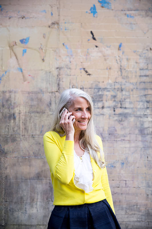 A mature woman talking on her phone by Ann-Sophie Fjelloe-Jensen for Stocksy United