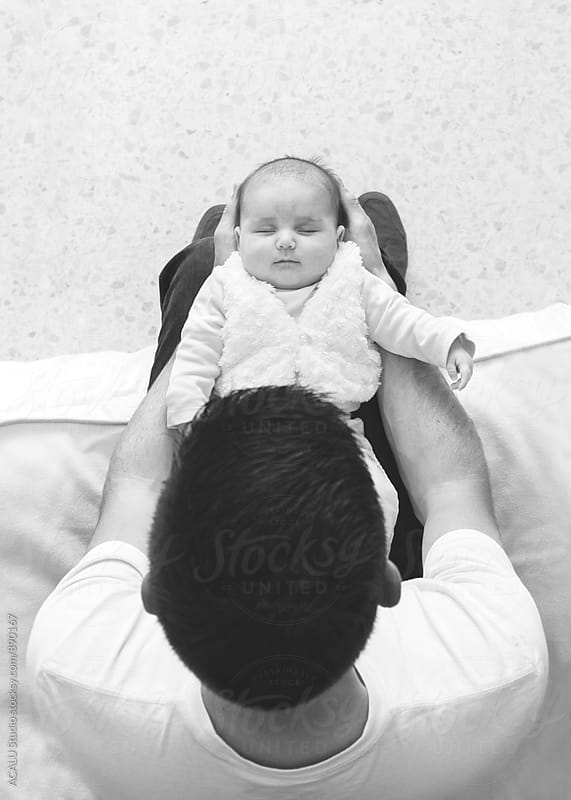Father with his daughter asleep in his arms by ACALU Studio for Stocksy United