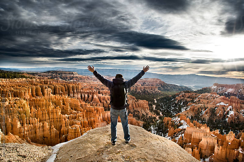 Man greets the world at dawn at the Bryce Canyon Utah by Jean-Claude Manfredi for Stocksy United