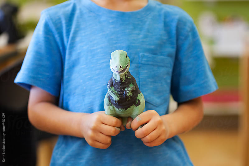 Young Boy Holding Painted Dinosaur Ceramic by Sean Locke for Stocksy United