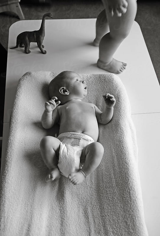 Newborn Baby on changing Table With Toddler Brother Near by Dina Giangregorio for Stocksy United